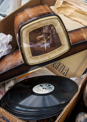 Time and Music boxed up. A vintage clock and vinyl LP's in a cardboard box, for sale at a flea-market. Mauerpark Flohmarkt, Prenzlauer Berg